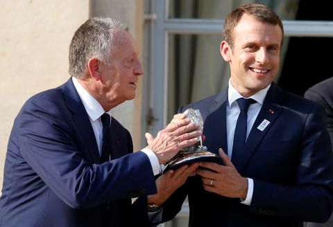 Olympique Lyon's soccer club head Jean-Michel Aulas (L) gives a gift to French President Emmanuel Macron (R) during a ceremony at the Elysee Palace in Paris, France, June 20, 2017 to celebrate the victory of Lyon's woman soccer team during the UEFA Women's Champions League. REUTERS/Geoffroy van der Hasselt/Pool