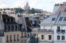 """(FILES) This file photo taken on June 30, 2013 shows roofs of buildings (front) and the Sacre-Coeur basilica (C) in Paris. The city of Paris on February 18, 2021 won an important victory against rental platforms such as Airbnb, after the court of cassation judged the regulation in conformity with European law, """"proportionate"""" and justified to fight against the shortage of rental housing. / AFP / Thomas SAMSON"""