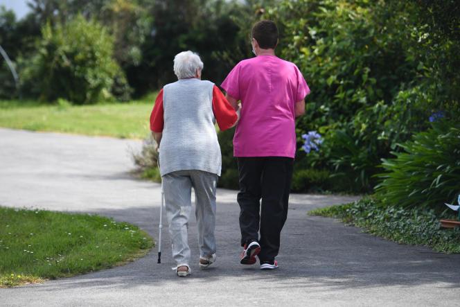 Une femme âgée, résidente en Ehpad à Ploudalmézeau (Finistère) marche avec une infirmière, le 23 juillet 2020.