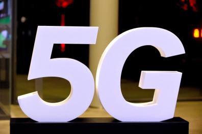 """(FILES) This file photo taken on October 9, 2018 during the inauguration of the Media group Altice' s Campus in Paris shows a 5G logo. Paris City Hall and telecom operators announced on February 19, 2021 that they have reached an agreement for the deployment of 5G """"in the coming weeks"""". the French capital still does not benefit from the latest-generation mobile network unlike several major French cities. / AFP / ERIC PIERMONT"""