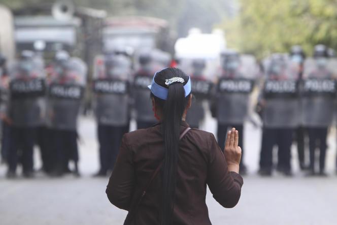 Une manifestante lève trois doigts en signe de résistance devant la police, à Mandalay, en Birmanie, samedi 20 février 2021.