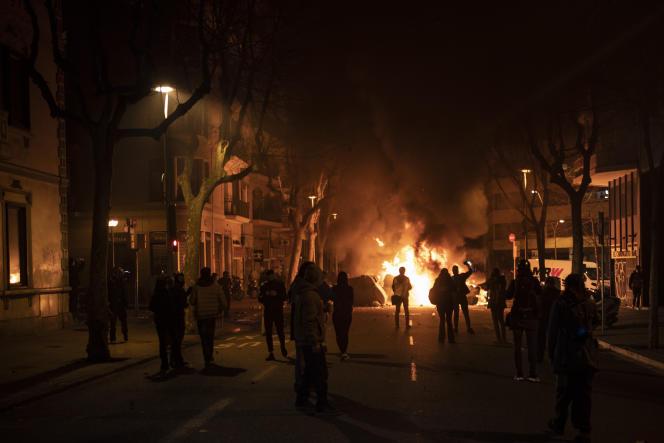 Des manifestants réunis près d'une barricade dressée lors d'une manifestation contre l'incarcération du rappeur Pablo Hasel, à Barcelone, le samedi 20 février 2021.