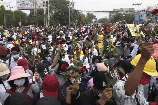 Des étudiants de l'université de médecine de Mandalay brandissant des fleurs durant une manifestation contre le coup d'Etat en Birmanie, le 20 février.