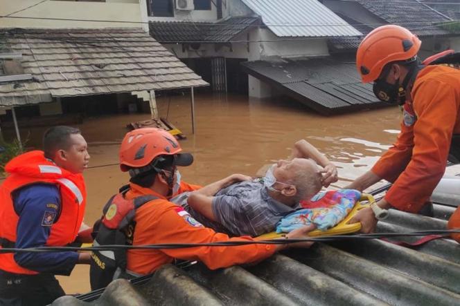 Los rescatistas indonesios llegan el 20 de febrero para ayudar a un anciano.