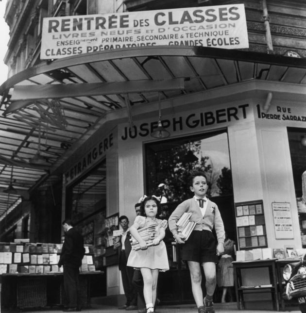 Le 20 septembre 1958, deux écoliers, les bras chargés de livres, sortent de la librairie Gibert Joseph à Paris. La rentrée des classes amène sa foule habituelle de clients pour l'achat de livres scolaires.