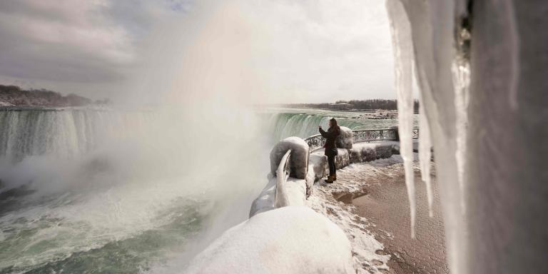 A woman takes a photo at the Horseshoe Falls in Niagara Falls, Ontario, on January 27, 2021. / AFP / Geoff Robins