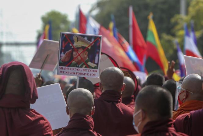 Des moines bouddhistes montrent une image défigurée du commandant en chef de l'armée birmane, le général Min Aung Hlaing, lors d'une marche de rue contre le coup d'Etat militaire à Mandalay, en Birmanie, vendredi 12 février 2021.