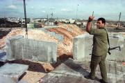 Erection d'une barrière à l'entrée de la colonie israélienne de Psagot, en Cisjordanie, en 1998. A l'arrière plan, Ramallah.