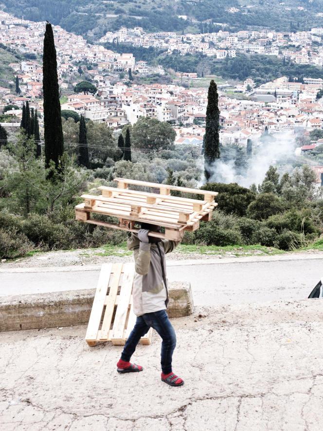 Un homme porte une palette vers le camp de réfugiés.