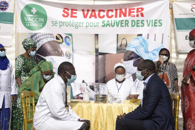Ablaye Diouf Sarr, le ministre de la santé et de l'action sociale (à droite), juste avant d'être vacciné contre le Covid-19, le 23février2021.