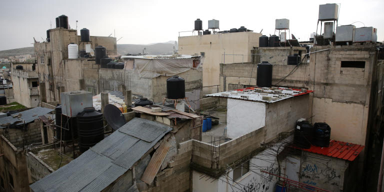 Giant water containers are seen on the rooftops of homes in the Balata refugee camp in Nablus on February 23,2021.(Photo by Heidi Levine for Le Monde)