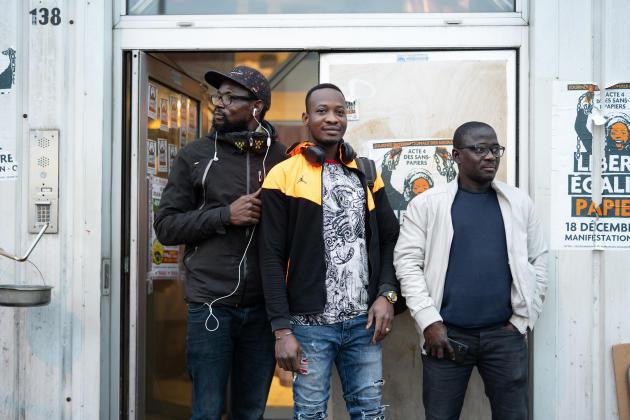 Kandé Touré, secrétaire général de l'association «Les Baras du 138 Montreuil» pose avec deux amis devant le bâtiment occupé par des travailleurs sans papiers, à Montreuil, le 20 février.