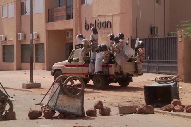 Des policiers anti-émeute se dirigent vers un groupe de manifestants à un poste de contrôle de fortune, à Niamey, le 24 février 2021.