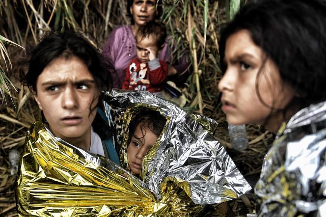 Dans cette photo d'archive prise le 28 septembre 2015, les réfugiés syriens sont couverts de couvertures de sauvetage à leur arrivée sur l'île grecque de Lesbos, après avoir traversé la mer Egée depuis la Turquie.