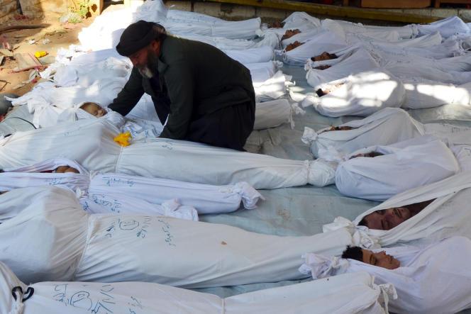 Le 21 août 2013, au lendemain de l'attaque chimique commise à Douma (Syrie), un homme tient le corps d'une enfant, victimedes gaz.
