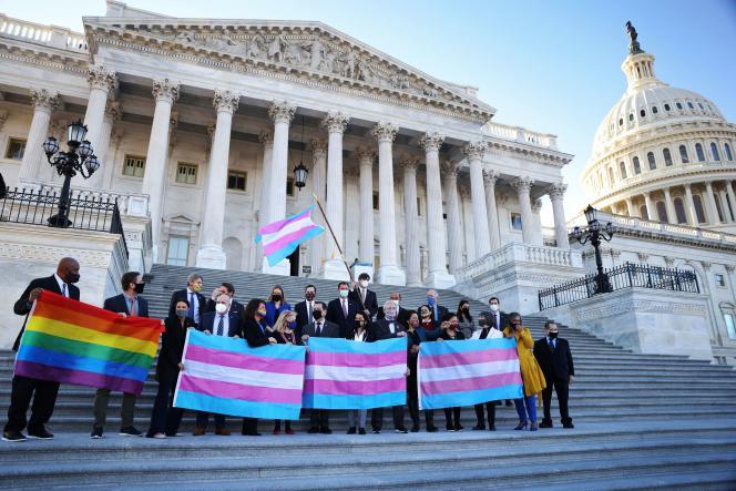 Des membres du Parti démocrate tenant les drapeaux LGBT+ et transgenre, sur les marches du Capitole, le 25 février à Washington, en amont du vote sur l'Equality act.