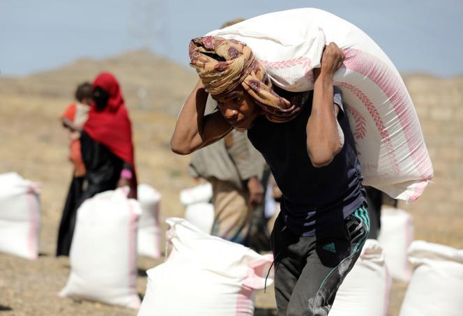 یک کارگر در اول مارس 2021 کیسه آرد تهیه شده توسط یک سازمان غیردولتی را به ذینفعان اردوگاه آوارگان در حومه صنعا یمن حمل می کند.