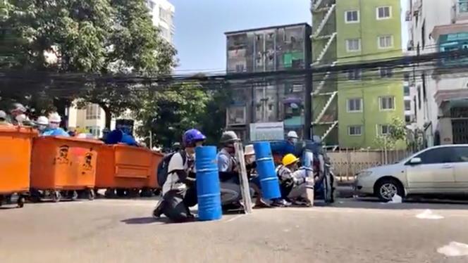 Des manifestants se protègent derrière des poubelles, jeudi4mars, à Rangoun, enBirmanie.