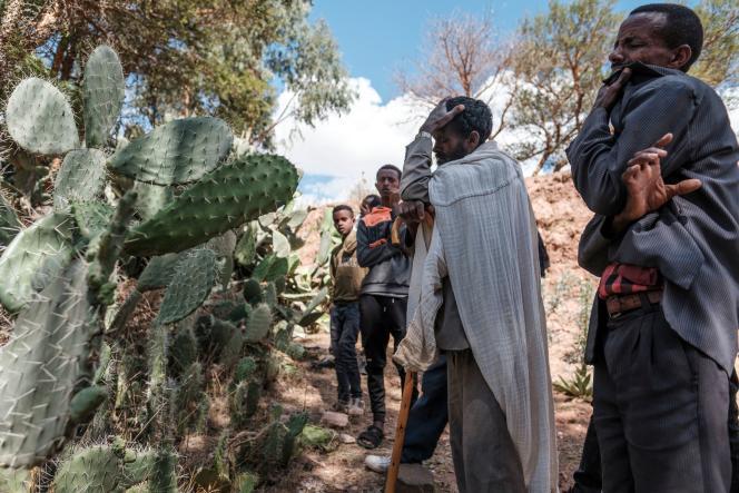 Des hommes se recueillent devant une fosse commune des victimes d'un massacre supposé avoir été perpétré par les soldats érythréens voisins dans le village de Dengolat, au nord de Mekele, la capitale du Tigré, le 26 février 2021.