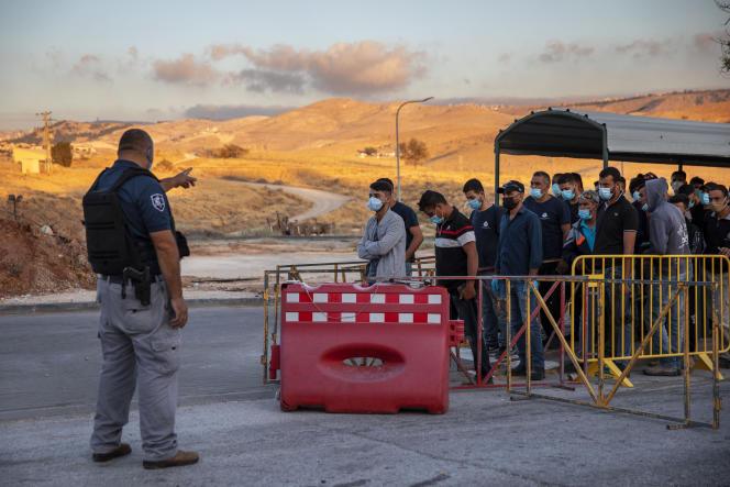 Des Palestiniens attendent pour traverser un point de contrôle, à l'entrée de la colonie israélienne de Maale Adumim, près de Jérusalem, en juin 2020.