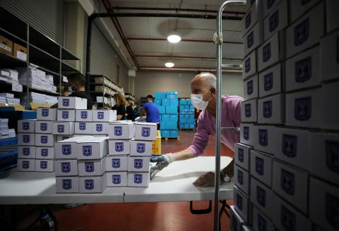 An employee wearing a mask moves boxes during a demonstration for the media revealing preparations ahead of Israel's upcoming election amid the coronavirus disease (COVID-19) crisis, at the Central Elections Committee's logistics centre in Shoham, Israel February 23, 2021. REUTERS/Ammar Awad