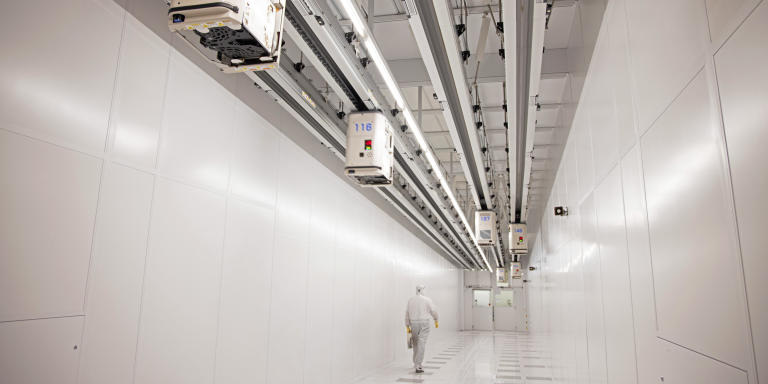 An employee passes beneath automated transport system cars carrying silicon wafer boxes in the clean rooms at the Globalfoundries semiconductor fabrication (fab) plant in Dresden, Germany, on Thursday, Feb. 11, 2021. The EU outlined a goal last year to produce at least one-fifth of the worlds chips and microprocessors by value, without giving details on how this would be achieved. Photographer: Liesa Johannssen-Koppitz/Bloomberg via Getty Images