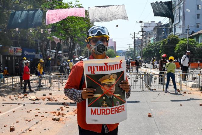 Seorang pengunjuk rasa dengan poster kepala tentara Burma, Jenderal Min Aung Hlaing, selama demonstrasi pada 9 Maret di Yangon.
