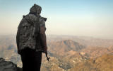 A fighter loyal to Yemen's Saudi-backed government keeps watch over a valley during clashes with Huthi rebel fighters west of the suburbs of Yemen's third-city of Taez on March 8, 2021. Yemen's six-year-old civil war pits the Iran-backed rebels against an internationally recognised government backed by a Saudi-led military coalition. / AFP / AHMAD AL-BASHA