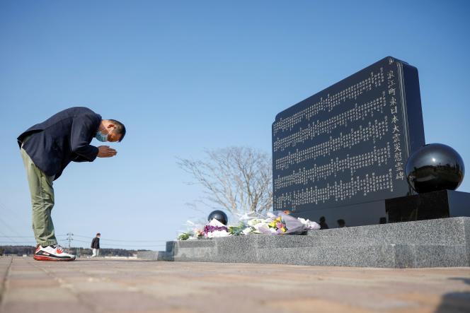 Un homme se recueille devant une stèle en hommage aux victimes de la catastrophe de Fukushima, au Japon, le 11 mars 2021.