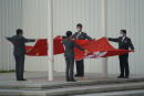 Staff members fold the Chinese and Hong Kong flags at the Legislative Council in Hong Kong, Thursday, March 11, 2021. China's ceremonial legislature on Thursday endorsed the Communist Party's latest move to tighten control over Hong Kong by reducing the role of its public in picking the territory's leaders. (AP Photo/Kin Cheung)