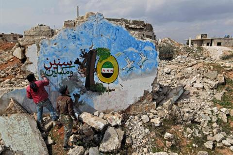 Syrians paint a mural on the remains on a building in the rebel held town of Binnish in Syria's northwestern province of Idlib, on March 11, 2021, marking the 10-years of the Syrian war. / AFP / Rami al SAYED
