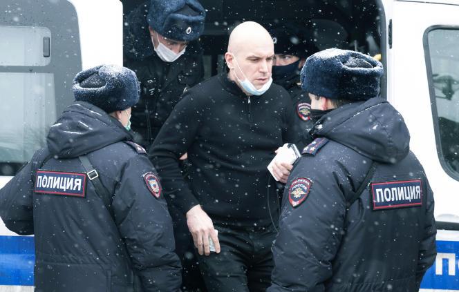 Ein Mann steht vor einem Polizeiauto, nachdem er wegen Teilnahme an einem politischen Forum der Opposition am Samstag, dem 13. März 2021 in Moskau festgenommen wurde.