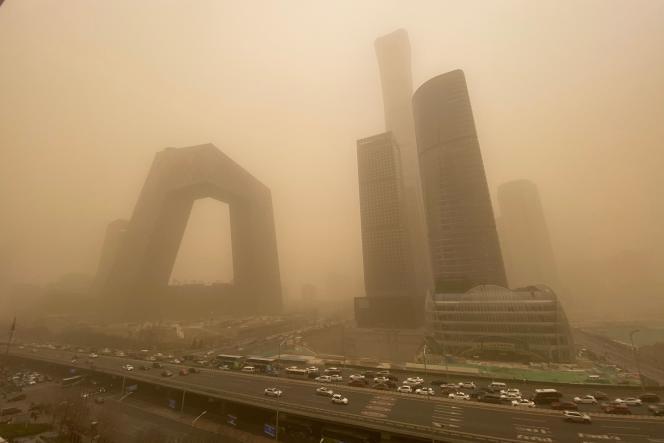 La torre de televisión pública china (izquierda) se ahogó en la niebla después de una tormenta de arena, el lunes 15 de marzo de 2021 en Beijing.