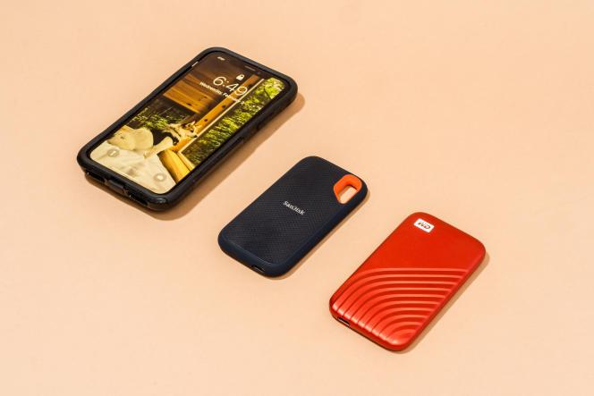 De gauche à droite: un smartphone (à titre de comparaison), le SSD portable Extreme V2 de SanDisk et le SSD My Passport de Western Digital.