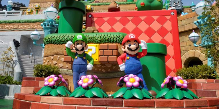 Mario and Luigi characters greet visitors in front of Yoshi's Adventure attraction inside Super Nintendo World, a new attraction area featuring the popular video game character Mario which is set to open to public on March 18, during a press preview at the Universal Studios Japan theme park in Osaka, western Japan, March 17, 2021. Picture taken March 17, 2021.  REUTERS/Irene Wang
