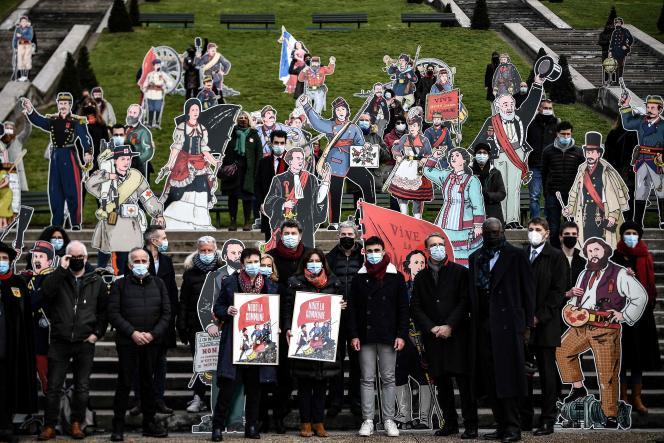 La Maire de Paris Anne Hidalgo (centre) pose aux côtés de silhouettes de communards, en face de la basilique du Sacré-Coeur, le 18 mars2021, pour commémorer les 150 ans de la Commune de Paris.