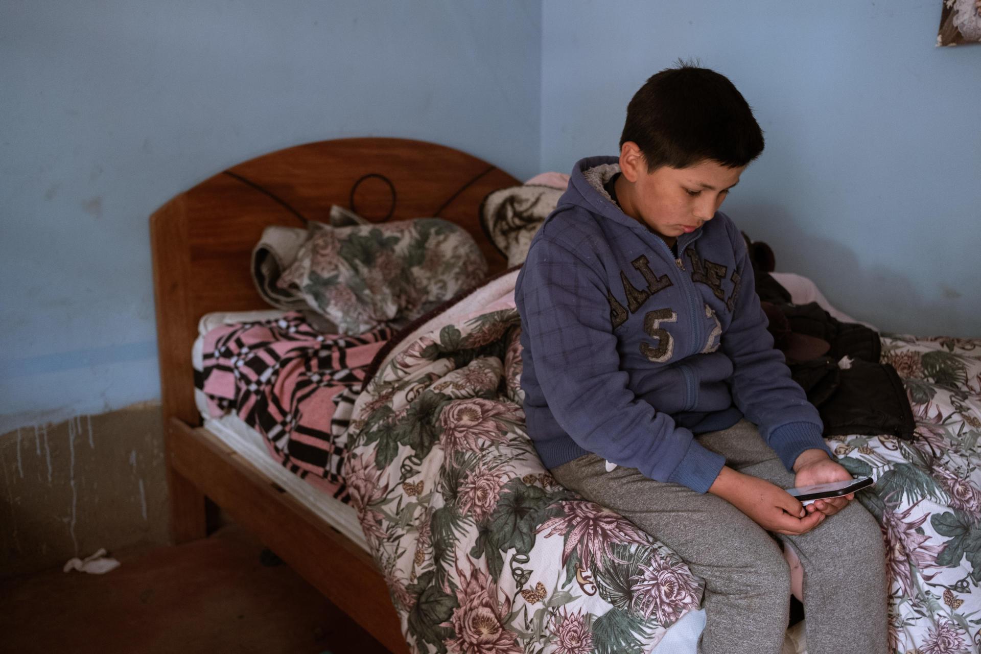 Aaron, âgé de 12 ans, commence ses cours virtuels le matin dans sa chambre, le 16 mars 2021. Il utilise le téléphone de sa tante pour se connecter et recevoir ses cours. Dans la communauté de Cuyo Grande (région de Cusco), les habitants n'ont pas de Wi-Fi et les parents doivent payer des forfaits pour avoir accès à Internet.