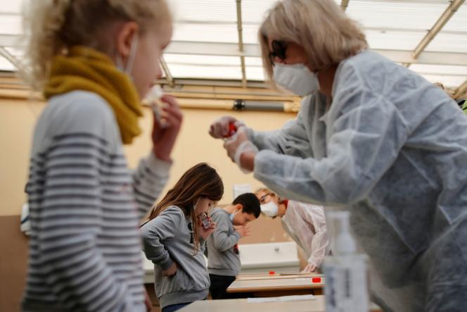 Des enfants effectuent un test salivaire,dans une école à Nice, le 8 mars 2021.