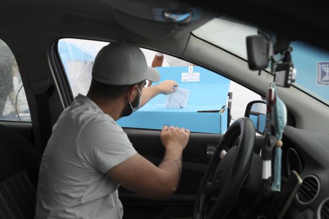 Un homme vote lors des élections législatives israéliennes depuis sa voiture, dans un drive destiné aux personnes malades du Covid-19, à Hadera, le 23 mars 2021.