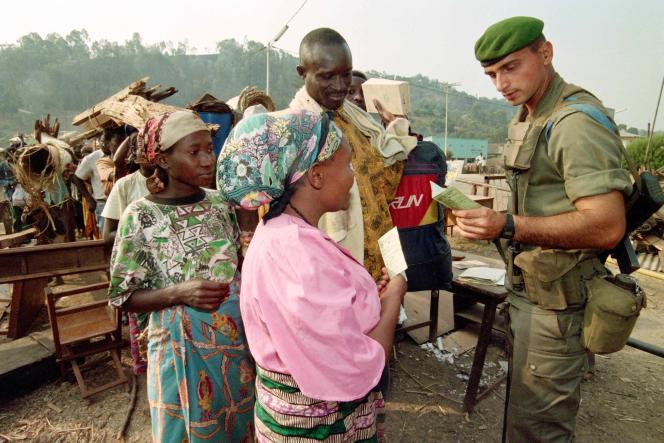 Un soldat de la Légion étrangère française vérifie les documents d'une femme rwandaise souhaitant traverser la frontière pour se rendre au Zaïre, le 15 août 1994.