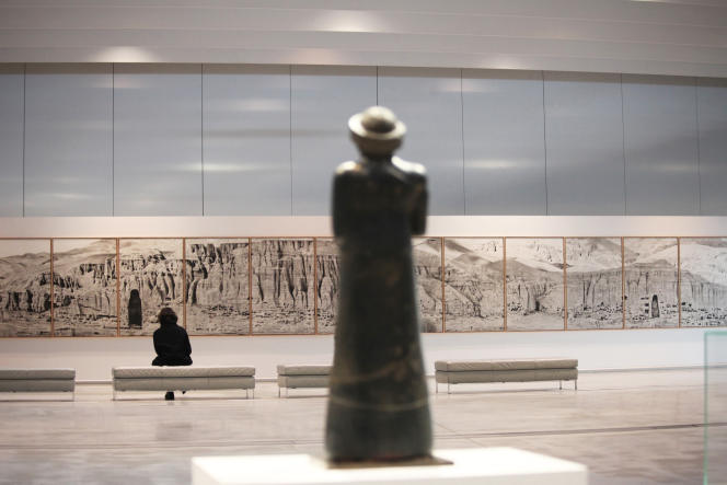 De dos, la statue en diorite noire du prince Gudea en prière (Basse Mésopotamie, vers 2120 av.J.-C.) face au panoramique de la falaise mutilée de Bamiyan, une œuvre de Pascal Convert exposée dans la Galerie du temps au Louvre-Lens.
