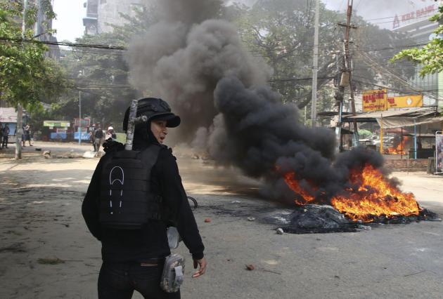 Los activistas a favor de la democracia protestan, mientras el ejército marcha frente a su líder en Rangún el 27 de marzo.