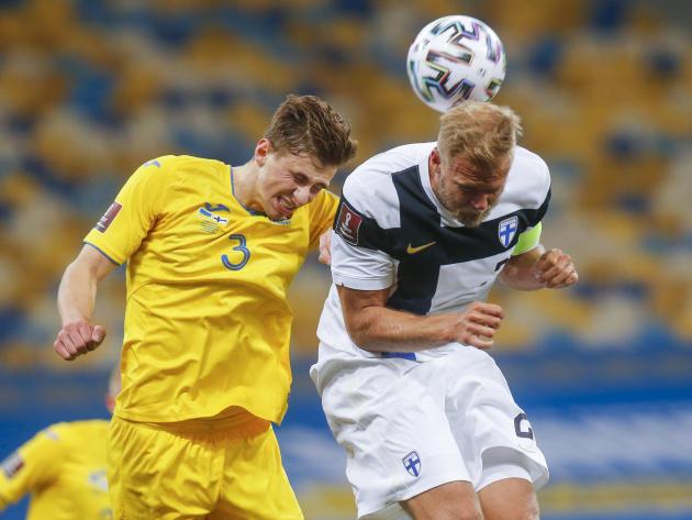 L'Ukrainien IIlya Zabarnyi, en jaune, et le Finlandais Paulus Arajuuri s'affrontent pour le contrôle du ballon, le dimanche 27 mars 2021, au stade olympique de Kiev.