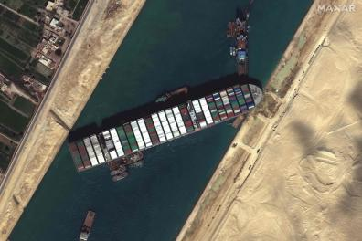 "CORRECTION / This satellite imagery released by Maxar Technologies shows tug boats and dredgers on March 27, 2021, attempting to free the Taiwan-operated MV Ever Given lodged sideways and impeding all traffic across Egypt's Suez Canal. The container ship, which is longer than four football fields, has been wedged diagonally across the entire canal since March 23, shutting the waterway in both directions. The blockage has caused a huge traffic jam for more than 200 ships at either end of the 193-km (120-mile) long canal and major delays in the delivery of oil and other products. - RESTRICTED TO EDITORIAL USE - MANDATORY CREDIT ""AFP PHOTO / Satellite image ©2021 Maxar Technologies"" - NO MARKETING - NO ADVERTISING CAMPAIGNS - DISTRIBUTED AS A SERVICE TO CLIENTS / AFP / Satellite image ©2021 Maxar Technologies / - / RESTRICTED TO EDITORIAL USE - MANDATORY CREDIT ""AFP PHOTO / Satellite image ©2021 Maxar Technologies"" - NO MARKETING - NO ADVERTISING CAMPAIGNS - DISTRIBUTED AS A SERVICE TO CLIENTS"