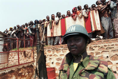 """A Ghanaian United Nations soldier watches over some Tutsi refugees 20 June 1994 in Kigali, as they are evacuated from the Holy Family church to Kabuga on the outskirts of the Rwandan capital. Some of France's partners in the Western European Union (WEU) are prepared to provide """"logistical support"""" to a proposed French-led military intervention to end ethnic bloodletting in Rwanda, WEU sources said 21 June. (Photo by ABDELHAK SENNA / AFP)"""