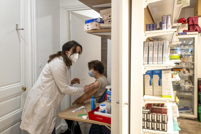 Hélène D, 70 ans, reçoit une première injection de vaccin. Pharmacie de la Place Denfert-Rochereau. Paris le 15 mars 2021.