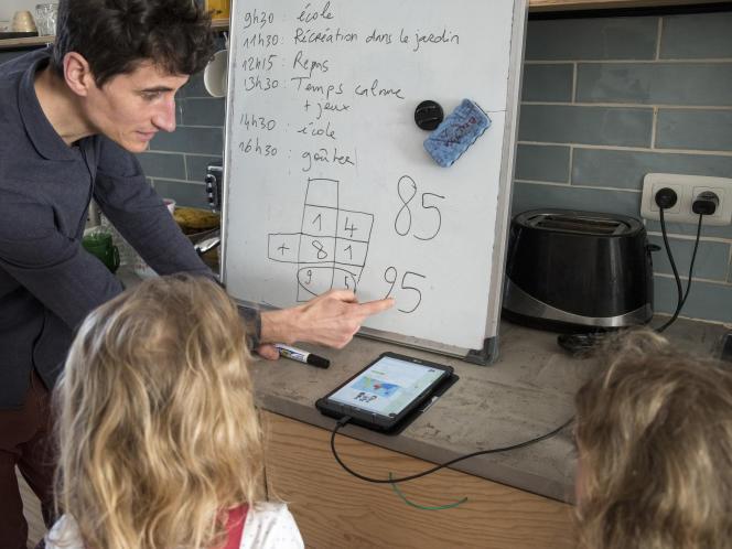 Lionel fait l'école à la maison à ses deux filles L. et R. lors du troisième jour du premier confinement, le 18 mars 2020, à Lille.