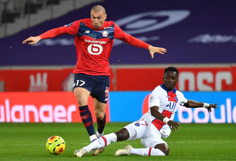 Lille's Turkish forward Burak Yilmaz (L) fights for the ball with Paris Saint-Germain's Senegalese midfielder Idrissa Gueye during the French L1 football match between LOSC Lille and Paris Saint-Germain, at the Pierre-Mauroy stadium in Lille, on December 20, 2020. (Photo by DENIS CHARLET / AFP)