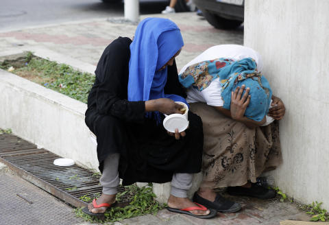 Two women hide their faces as Ethiopian domestic workers who were dismissed by their employers gather with their belongings outside their country's embassy in Hazmiyeh, east of Beirut, on June 24, 2020. - Around 250,000 migrants -- usually women -- work as housekeepers, nannies and carers in Lebanese homes, a large proportion Ethiopian and some for as little as $150 a month. None are protected by the labour law. (Photo by JOSEPH EID / AFP)