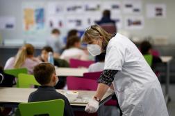 Une personnelle d'une école discute avec un enfant, dans la cantine d'une école privée à Saint-Sébastien-sur-Loire, le 2 avril 2021.